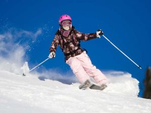 Girl riding on skis with bright blue sky on the background
